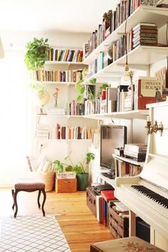 Just gorgeous. I love the open shelving and the plants interspersed between the books. And the color of that piano! So unique.