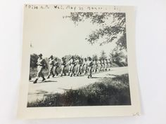 Black and White Photograph of Soldiers marching on Memorial Day  Photo shows a line of soldiers with rifles. Buildings in the background. 3.5 by 3.5 inch Black and White