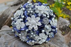 This bouquet features silver and pearl rhinestone jewelry with some pearls and faceted glass beads wired in. The filler flowers are a deep blue and I've added swarovski rhinestones to the petals. The bouquet is finished with a blue ribbon, which can be changed ot another color, and there are jeweled accents on the handle. Lovely!