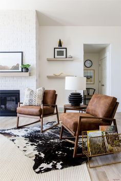 Leather couches living room Layered rugs Living room cabinets Couches living room Tan sofa living room Transitional home decor - Crisp white walls layered rugs and the unmistakable form of our - Rugs In Living Room, Living Room Chairs, Living Room Designs, Tan Sofa Living Room Ideas, Room Rugs, Cozy Living, V Shaped Living Room, Earth Tone Living Room Decor, Living Room White Walls