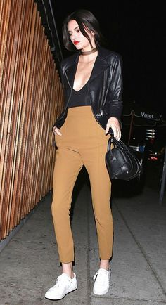 Kendall Jenner wears a bodysuit, moto jacket, cropped trousers, and white sneakers