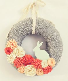yarn wrapped wreath [this is cute for easter but for everyday I think you could get away with colorful various sized balls of yarn for your 'flowers' and hang with a multi-colored hank of other yarn. jh]