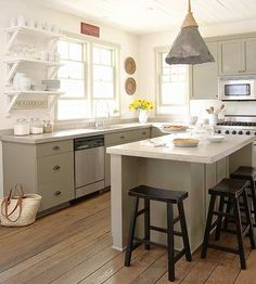 I like most things about this kitchen - grey cabinets, no upper cabinets, LOVE the island light fixture.  DON'T like the white countertops!  I think it would be better with wood/brown stained concete