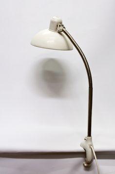 Oude bureaulamp met tafelklem. De lamp is ontworpen door Christian Dell en uit de Kaiser iDell Original serie. De kap is wit/creme van kleur en door het flexibele gedeelte van de lamp in allerlei posities te richten. Te dateren rond de jaren 30.