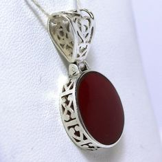 """Reversible Sterling Silver Silpada Red Stone Filigree Pendant  Featuring a 17.15 x 14.65mm oval red stone cemented and flush set, the piece is embellished throughout with lovely filigree patterns. Equipped with a hinged bale containing an opening of .420 x .285"""" for a chain to pass, the piece can be worn to display the crimson stone or the mandala-like pattern on its reverse. The base of the bale is stamped """"925"""" along with the Silpada makers mark. It weighs 2.25dwt."""