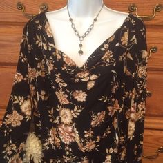 """Briggs New York Floral Blouse 90% polyester and 10% spandex so it has a lot of stretch. Approximately 25"""" in length and when laid flat from armpit to armpit  it measures 24"""" across.  Background is black with a tan and white floral pattern on it.  Very good condition.  Feels like a liquid knit and really doesn't wrinkle.  Briggs New York Tops Blouses"""