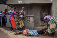 Ebola epidemic, October 2014. Waterloo, Sierra Leone. Women react as volunteers take away the body of a woman who died of Ebola. Photograph: Florian Plaucheur/AFP/Getty