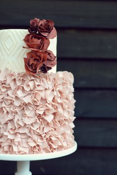 Fun confetti style ruffles in blush on a small two tiered wedding cake. Ivory and white ikat fondant design adorned with marsala sugar ranunculus. Country Cake Shop