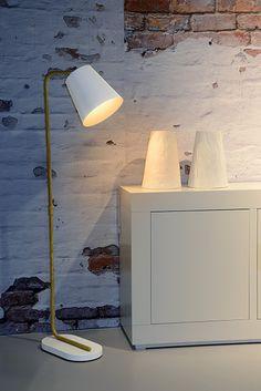 Lampa podłogowa CONA to minimalistyczna lampa stojąca w stylu skandynawskim. Wykonana jest z wysokiej jakości metalu. Stalowa noga z motywem drewna to dekoracyjny element tej lampy. Dość duży biały metalowy klosz skrywa źródło światła z gwintem E27 (brak w komplecie). Klosz jest ruchomy, dzięki czemu można dopasować kierunek świecenia lampy do potrzeb. W serii dostępna jest także lampa w kolorze czarnym oraz lampki biurkowe.