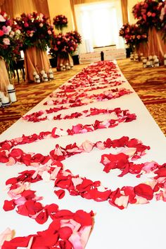Rose petals shaped in continuous hearts down a wedding aisle.