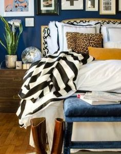 Bold blue wall, graphic striped blanket, and hotel bedding