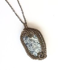 """This is a very unusual weathered Agate with shades of blues running through it and white veins. I have used a high quality enamelled copper wire in gunmetal to bring out the beauty of the stone and finished it with an 18"""" gunmetal chain. The length can be altered if desired.    It would look stunning with jeans or any outfit for any occasion and like most of my designs is freeform and therefore a one off.    I post 1st class in 1-2 days in a padded envelope. If you wish to have a luxury…"""