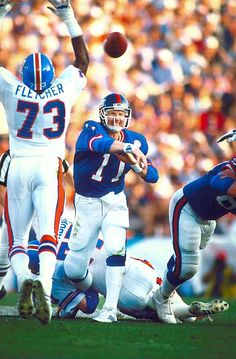 New York Giants quarterback Phil Simms tosses a pass around the outstretched arms of Denver Broncos linebacker Simon Fletcher. Simms carved up the Broncos defense for 268 yards and three touchdowns on passing as the Giants dominated Denver New York Giants Football, Nfl Football, Football Players, American Football, Football Memes, Football Shirts, College Football, Super Bowl Xxi, Americana Retro