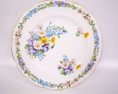 Vintage Roslyn Fine Bone China Dessert Plate Made in England Garland Pattern  This is a pretty fine bone china by Roslyn. It is made in England and is in the GARLAND pattern.  This dessert plate measures 7 in diameter with a scalloped gold trim edge.  This plate is in excellent condition with no chips, no cracks, and no scratches.  This a beautiful piece to add to your collection