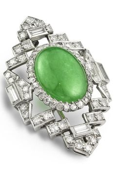 An Art Deco jade and diamond brooch, circa 1920. The stylised oval brooch with the central oval jade surrounded by thirty-one small millegrain set round diamonds, with a baguette-cut diamond to top, bottom and each side, with channel-set diamond rectangles to give an openwork effect, overall measurements approximately 40 x 24mm.
