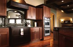In this transitional kitchen, contemporary and traditional elements are melded into one comfortable design. The kitchen flows naturally out of the living room, dining room and entry in this creative open floor plan. An L-shaped kitchen with a diagonal island is both attractive and functional. Note how dark and light elements work together to create dramatic visual contrasts.