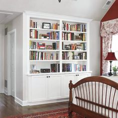 Separate cabinets and shelves, modeled after the living room built-ins that came with the house, symmetrically frame the passageway to a bath in this master suite. | Photo: Tria Giovan | thisoldhouse.com