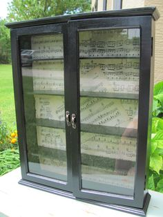 black curio cabinet with vintage music/ instead I want vintage wine lists and display glass stemware