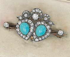 AN ANTIQUE TURQUOISE AND DIAMOND BROOCH designed as two pear-shaped turquoise cabochon and old-cut diamond clusters surmounted by a diamond-set ribbon to the twin knife-edge bar with diamond collet terminals, mounted in silver and gold, circa 1890