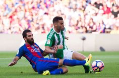 Arda Turan (L) of FC Barcelona fights for the ball with Bruno Gonzalez of Real Betis Balompie during the La Liga match between FC Barcelona and Real Betis Balompie at Camp Nou on August 20, 2016 in Barcelona, Catalonia.