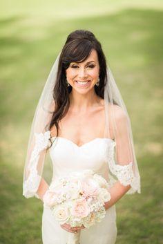 Voluminous half up-do, mid-length lacy veil, loose curls, bangs, formal wedding hair // Nate Messarra Photography