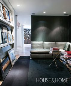 Dark walls and a dark rug heighten the coziness of the den, in sharp contrast to…