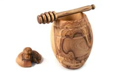The lush bi-colored swirls of natural olive wood grain elevate this honey pot from a simple vessel into a work of art. Smoothly sculpted ridges mimic the shape of a beehive on the exterior, and a notc