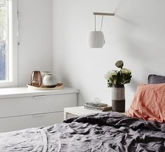 All white bedroom, navy bedding, and white wall mounted sconce