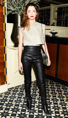 A gold crop top is worn with shiny high-waisted pants, lace-up booties and a sequin shoulder bag.