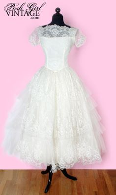 1950's adorable Tea Length Lace Wedding Dress:   Short sleeves & chest is sheer with sequins in front, fitted bodice and a very full and frilly lace skirt. White lace and tons of white tulle over an ivory acetate liner. Metal zipper in the back, skirt has 4 layers. The back of the skirt has tiers of tulle and the front has sheer lace. A gorgeous combination & style.