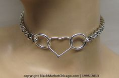 <p> Simply, chic and shiny, this stainless steel, flat link chain day collar features a center open heart ring, accompanied by 1/2-inch silver-plated O-rings and a mini (3/4-inch) heart-shaped padlock rear closure. It's REVERSIBLE; wear it either way. Two keys (also heart-shaped) are provided for the padlock.</p>