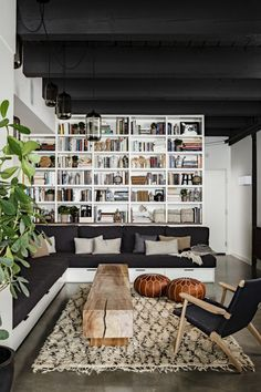 wall of books* contrast* moroccan poufs* antique wood* what a cozy lovely space*