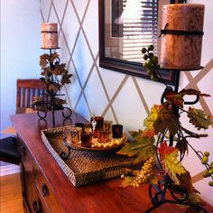 Simple fall themed dinning room decore. Wrap fall themed garland from the dollar store around candle holders. That's it!