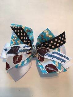 CELEBRATE THE CAROLINA PANTHERS! This 4-layer, glitzy, turquoise and silver chevron handmade hair bow is constructed with care and high-quality materials.  **The size of the pictured bow is a 6-inch Large, but can be ordered in other sizes. Hair bows may be made with a french barrette (as shown) or an alligator clip.  Item Details: *Ribbon Type: Base Ribbon: White Grosgrain (1.5) Middle Layer- turquoise and glittery silver chevron grosgrain (width: 1.5) Top Layers- Panther logo, football…