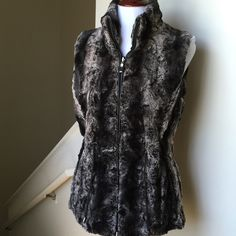"""NWOT Faux Fur Vest W Tie Waist & Pockets NWOT! I took the tags off of this but I never wore it. Pretty much brand-new. Beautiful Faux Fur Vest with Tie Waist & Faux Leather Lined Pockets. The ties at the waist make this vest so beautiful because it really accentuates the waist. This best also zips closed and has a faux leather lining along the zipper. Beautiful black and gray color. 100% polyester. Size Small.  Bust 17""""; length 25.5"""" Gallery Tops"""