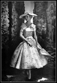 Model in lovely garden-party dress of white organdy printed with pink roses, matching wide-brimmed hat, by Lanvin-Castillo, photo by Georges Saad, 1955