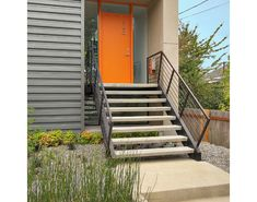 "Exterior Ideas: 12 Brightly Colored Front Doors -- Seattle-based Elemental Design used ""Benjamin Moore ""Blaze Orange"" paint for the front door on this modern home with corrugated steel siding and Zen-like landscaping."