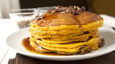 Pumpkin spiced pancakes topped with maple syrup and toasted pecans. The perfect fall breakfast!