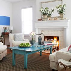 Surrounded by chairs and popping against the clean white interior, a distressed blue coffee table serves as the focal point of this family room. To make pops of color stand out even more in a neutral room, repeat bright colors only a few times, such as in one or two pieces of artwork or accessories.