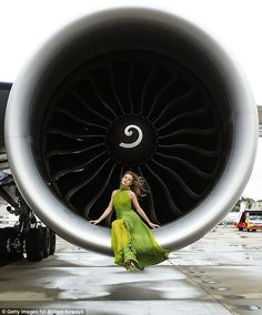 Spinning around: The model-of-the-moment posed inside one of the large airplane engines before the fashion show #aviationweddingideas