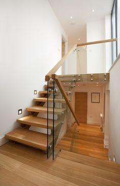 Trevanion home remodel, Cornwall. Split level staircase, glazed balustrade, glass and wood stairs. Photography by Alison White.