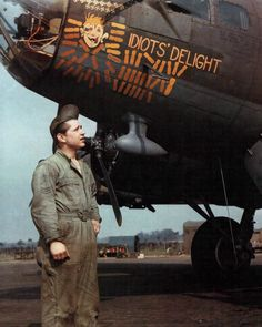 """B-17 Bomber Color Nose Art Sgt. Penrose A. Bingham of Reading, PA stands in front of the B-17 """"Idiots' Delight"""" in England in WWII. """"Idiots' Delight"""" served with 94th BG / 332nd BS and 447th BG / 710th BS. (U.S. Air Force Photograph.)"""