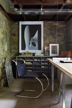 """Christina's office is in a section of the basement that opens to the garden. She runs her own interior design firm, Takatina, and works with Taka on jobs that require an architect. The table is made from a hollow-core door — """"the cheapest you can find at Home Depot,"""" says Taka — and metal sawhorse legs. The desk chair, the Mies van der Rohe MR Chair from Knoll, was a bigger splurge."""