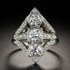 This dynamic (and aerodynamic) Art Deco dazzler, hand-fabricated in platinum during the peak of the period - circa 1925 - sizzles front an center with a vertical trio of bright white, high-quality, European-cut diamonds, together weighing one-and-a-half-carats (.50 carat each). The streamlined jewel is elegantly designed with simple, yet striking, geometric style. 7/8 inch long, lustrous and lovely. 1.85 carat total diamond weight, currently ring size 6.