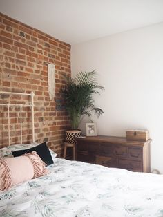 Master bedroom with exposed brick wall and vintage furniture