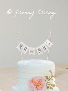 This cake topper of the banner is amazing. And the bright splash of color with the flower is genius.  ~A