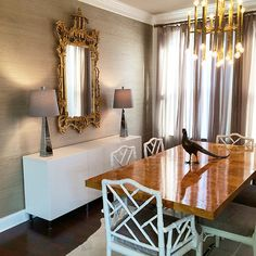 White and taupe dining room features a Jonathan Adler Meurice Chandelier illuminating a stainless steel and burl wood dining table, Bond Dining Table, lined with white bamboo dining chairs atop a metallic zebra cowhide rug.