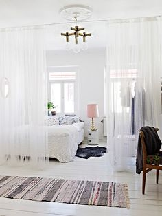 Love the use of sheer curtains to divide spaces in the room. Clever and pretty. Good idea for studio apt.