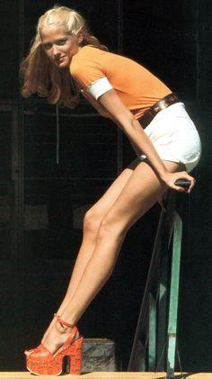 Orange plastic platform shoes and white hot pants
