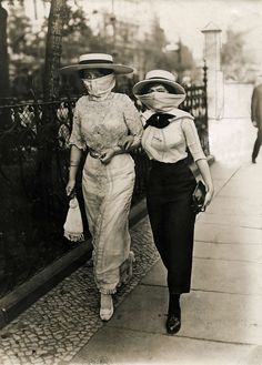 "1913, unknown location: A striking image from the Netherlands national archive. At first look I wondered if they were influenza masks - the first years of the century had plenty of epidemics. Original caption: ""Two wives of American millionaires in long skirts started wearing a veil, emulating the style of Berlin women. They walk arm in arm down the street. Location unknown, 1913."""